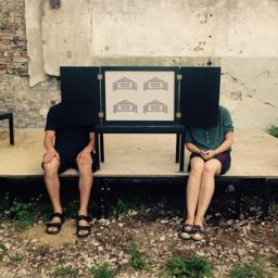 Na fotografii dwie osoby chowają się za skrzyneczką teatrzyku kamishibai.