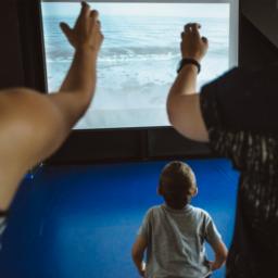 Dwoje dorosłych i dziecko, patrzą na ekran. Na ekranie - morskie fale. Osoby dorosłe wyciągają ręce w stronę ekranu.