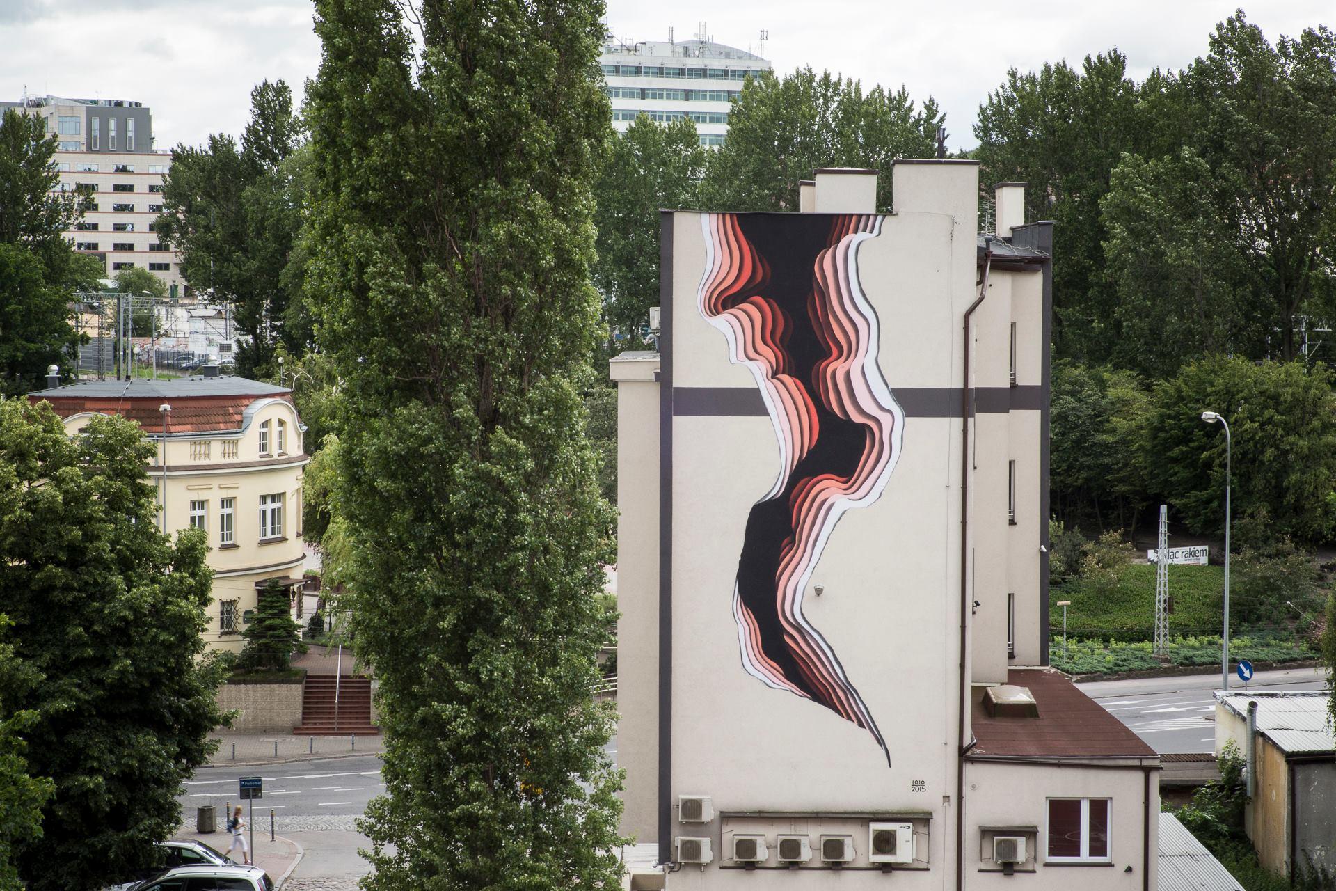 Ozdobny mural, który przypomina dużą dziurę w ścianie. Czarna otchłań otoczona jest kolorami.