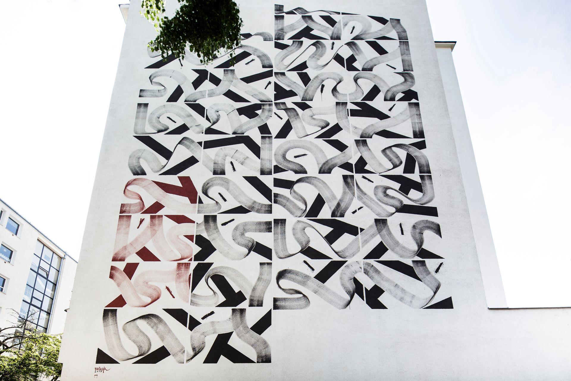 Ozdobny czarno-biały mural wykonany przez artystę o pseudonimie Blaqk.