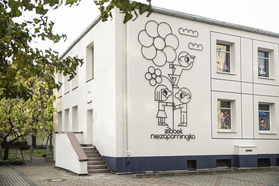 """Na zdjęciu widać ścianę budynku z dużą metalową ozdobą. Metalowe linie układają się w kształt trójki dzieci i napis """"Żłobek niezapominajka""""."""