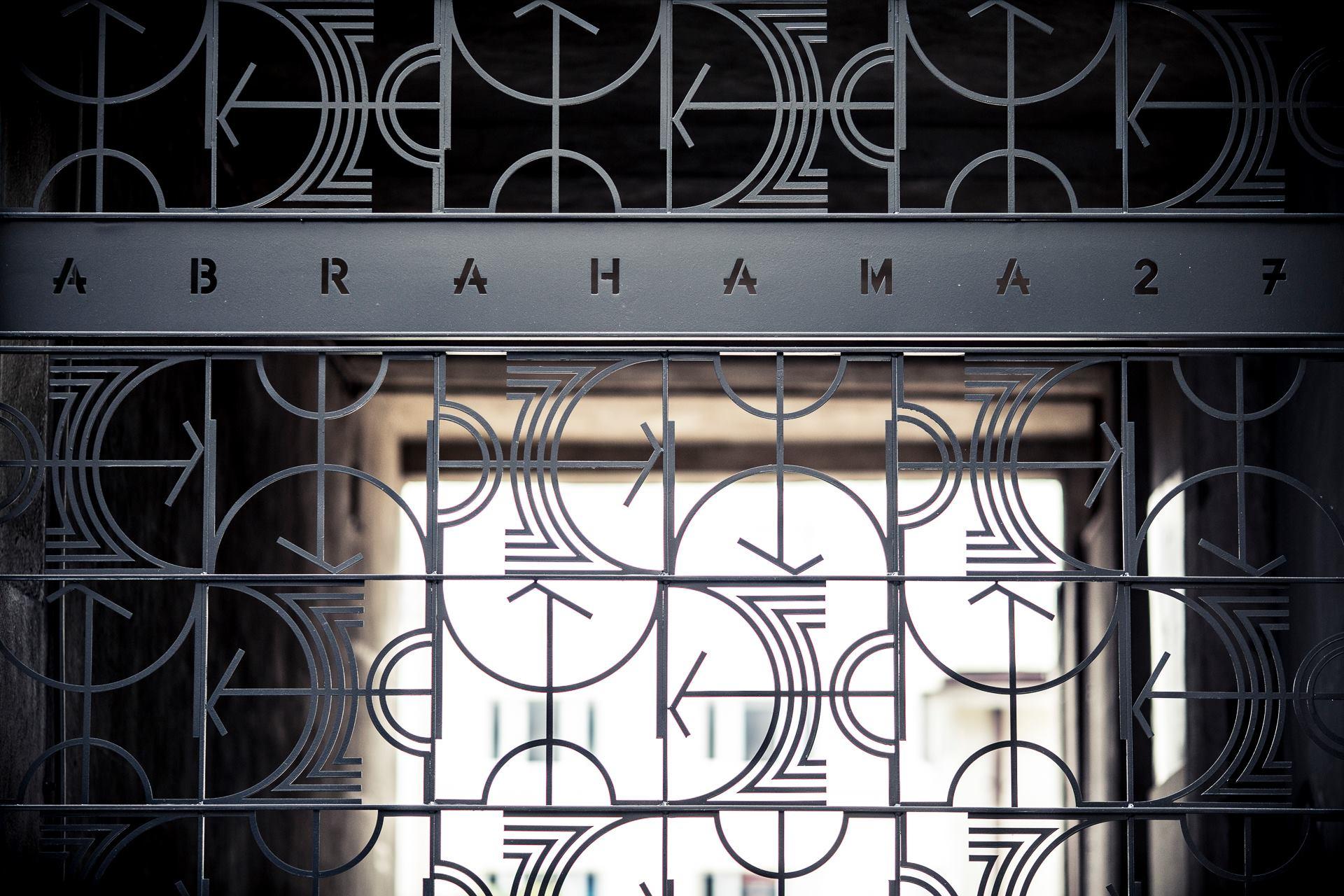 Fotografia przedstawia metalową bramę z dekoracyjnym wzorem.