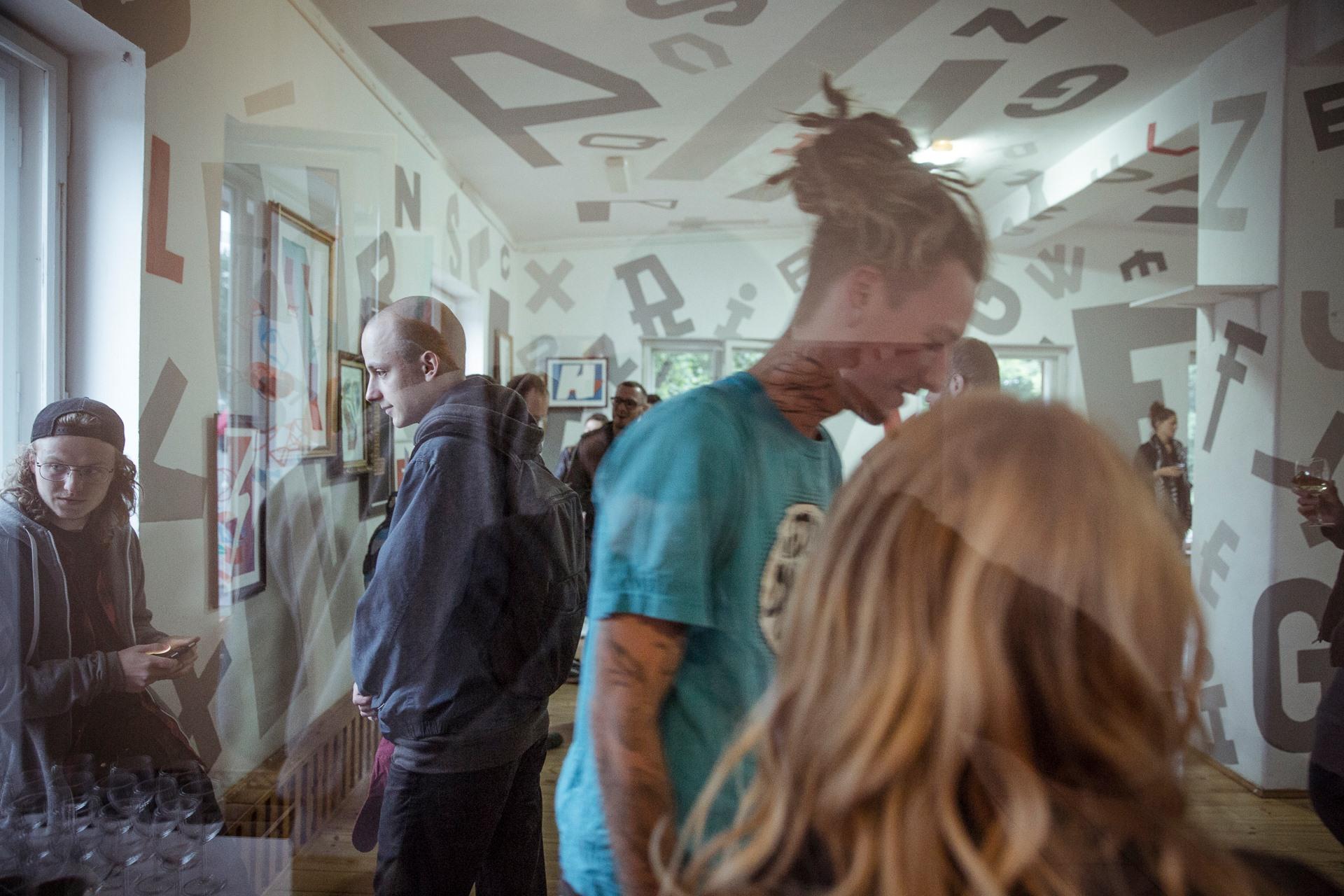 Wernisaż w tuBAZIE. Na zdjęciu widać grupę ludzi i ściany pomieszczenia ozdobione dużymi literami.
