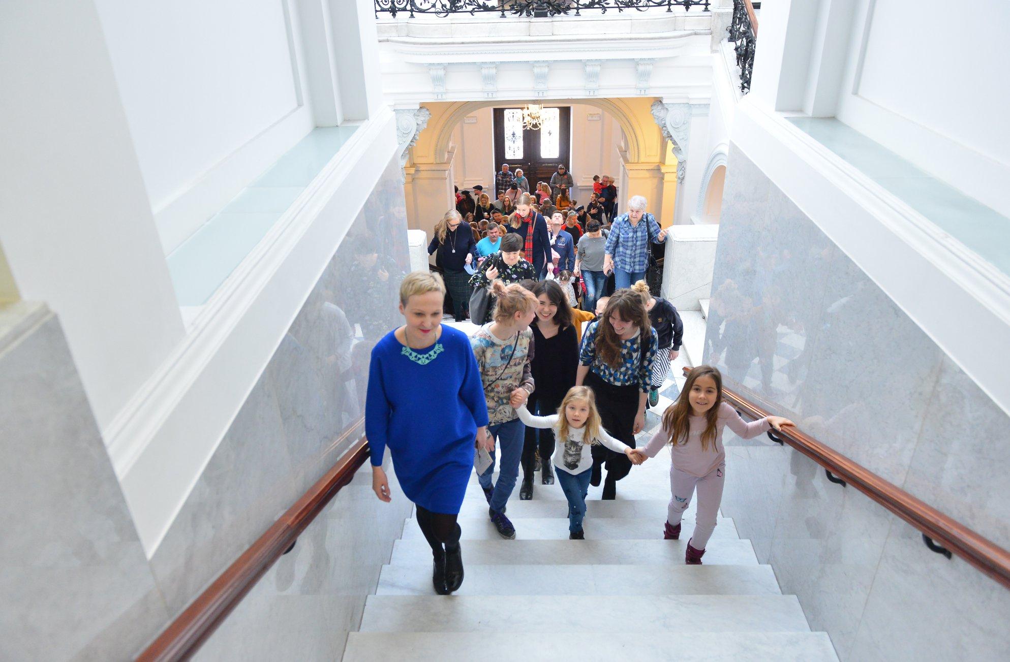 Ewa Solarz prowadzi grupę dzieci i rodziców po schodach galerii.