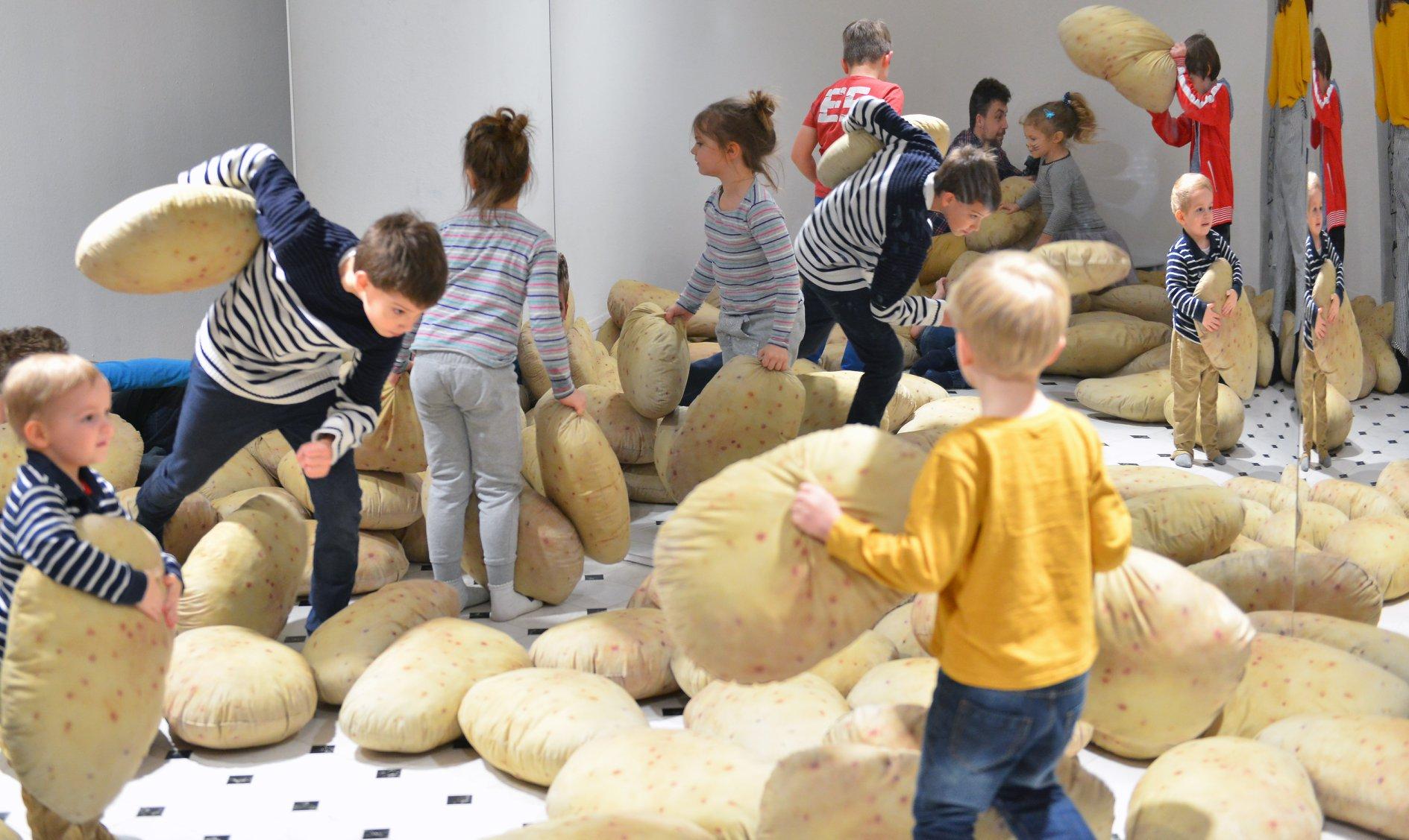 """Wystawa """"Wszystko widzę jako sztukę"""". Na zdjęciu grupa dzieci bawi się wielkimi poduchami ziemniakami."""