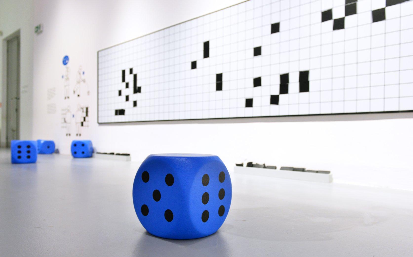 """Wystawa """"Wszystko widzę jako sztukę"""". Na zdjęciu widać duże, niebieskie kostki do gry leżące na podłodze galerii."""