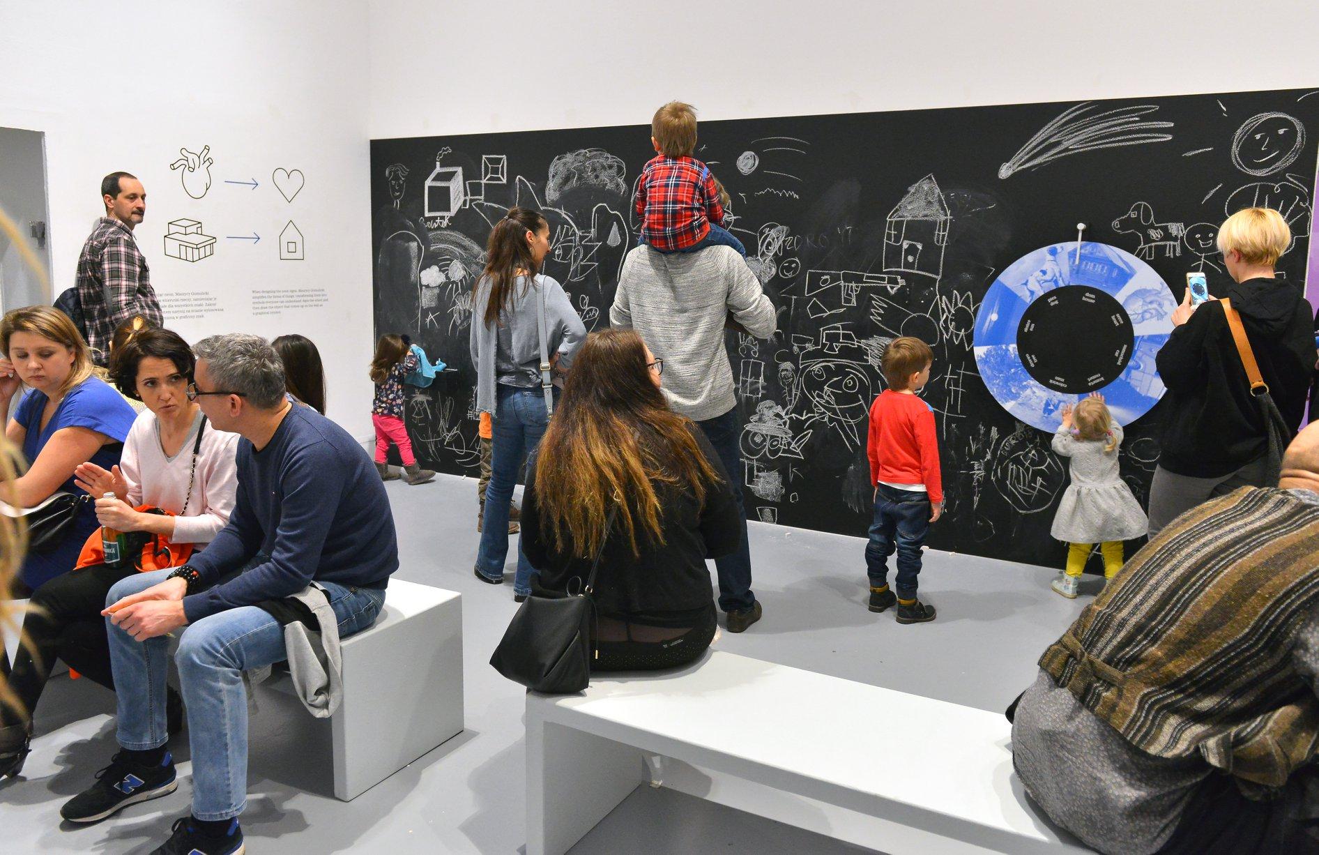 """Wystawa """"Wszystko widzę jako sztukę"""". Dzieci i rodzice oglądają rysunki kredą na czarnej ścianie."""