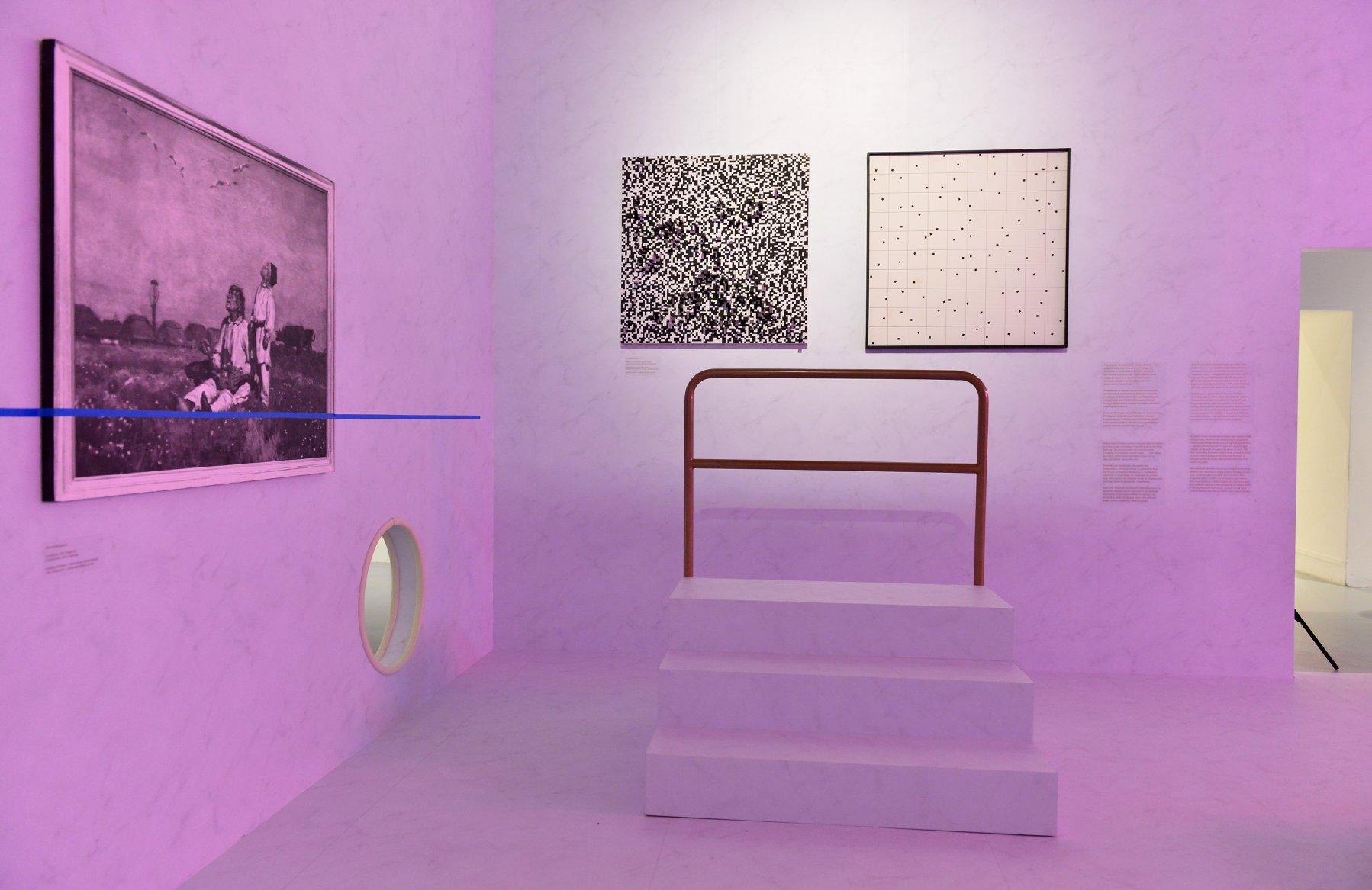 """Wystawa """"Wszystko widzę jako sztukę"""". Przestrzeń galerii wypełnia fioletowe światło. Na ścianach wiszą prace. Na podłodze stoją małe schodki z barierką."""