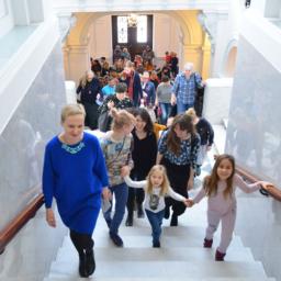 Na zdjęciu widać Ewę Solarz, prowadzącą dzieci i dorosłych po schodach galerii.