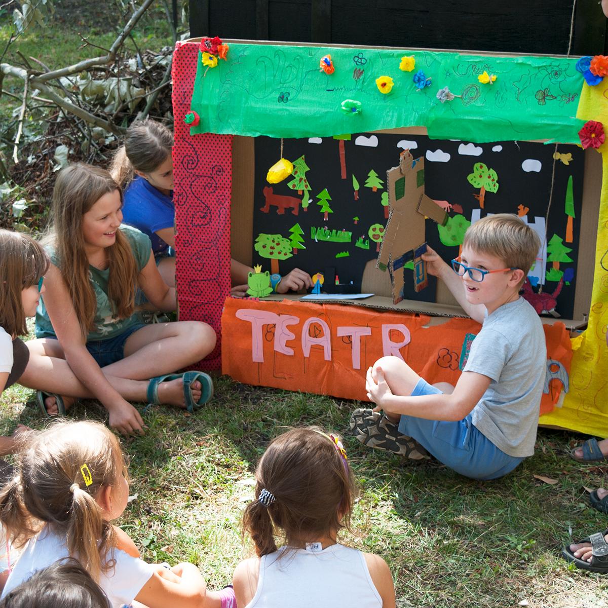 Na fotografii widać teatr z dużego kartonu i papierów, stworzony przez dzieci. Wokół papierowej sceny, na trawie, siedzą mali twórcy. Troje z nich odgrywa spektakl przy użyciu papierowych kukiełek, a reszta patrzy.