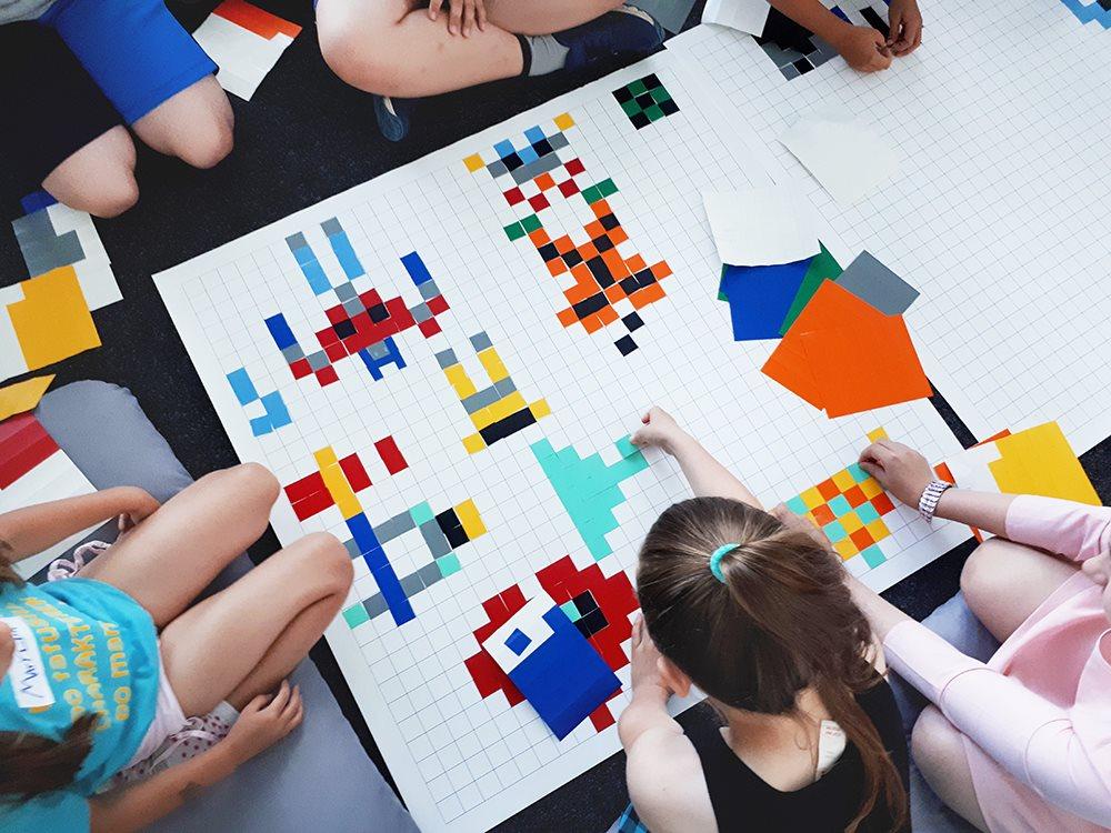 Na fotografii widać dzieci układające obraz z kolorowych kwadracików.