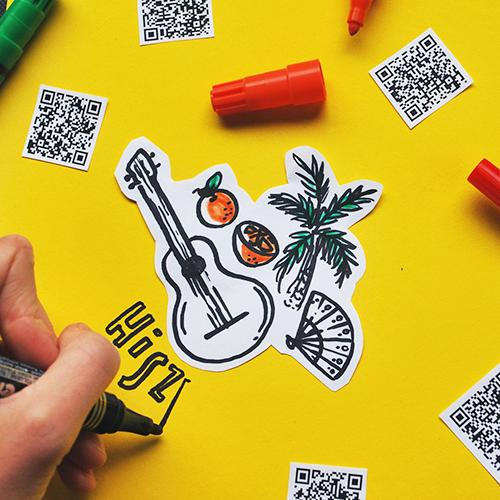 Na zdjęciu widać rękę rysującą na kartce. Wokół leżą rozrzucone kody QR.