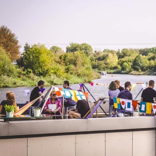 Na zdjęciu ludzie rozmawiają w parach. Wokół nich wiszą różnokolorowe flagi, a w tle widać zieleń i rzekę.