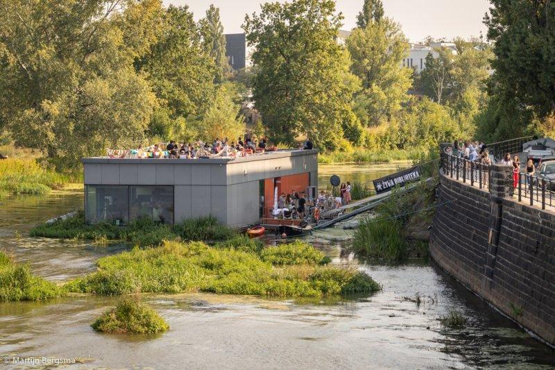 Żywa biblioteka. Na zdjęciu widać budynek unoszący się na wodzie. Grupa osób wchodzi do budynku po kładce.