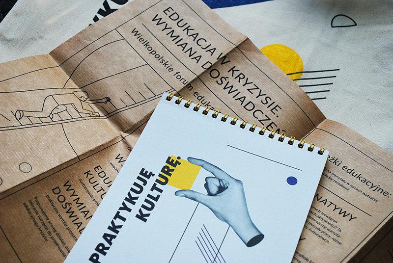Na zdjęciu widać materiały drukowane z Konferencji Miasto i Kultura i Forum Edukacja w kryzysie: ulotkę, notes i torbę w tle.