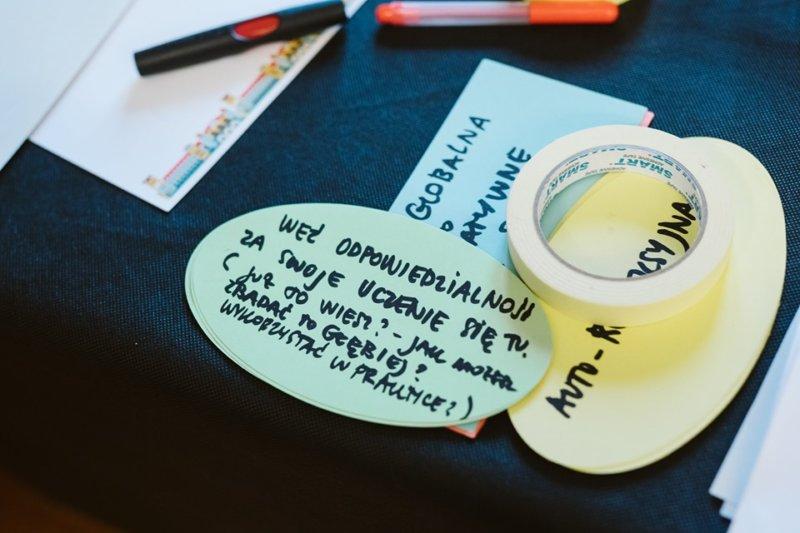 Fotografia przedstawiająca notatki na papierze i przybory do pisania.