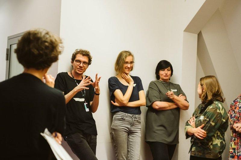 Fotografia pokazująca warsztaty. Kilka osób stoi pod ścianą, dwie coś mówią. Pozostałe osoby słuchają.