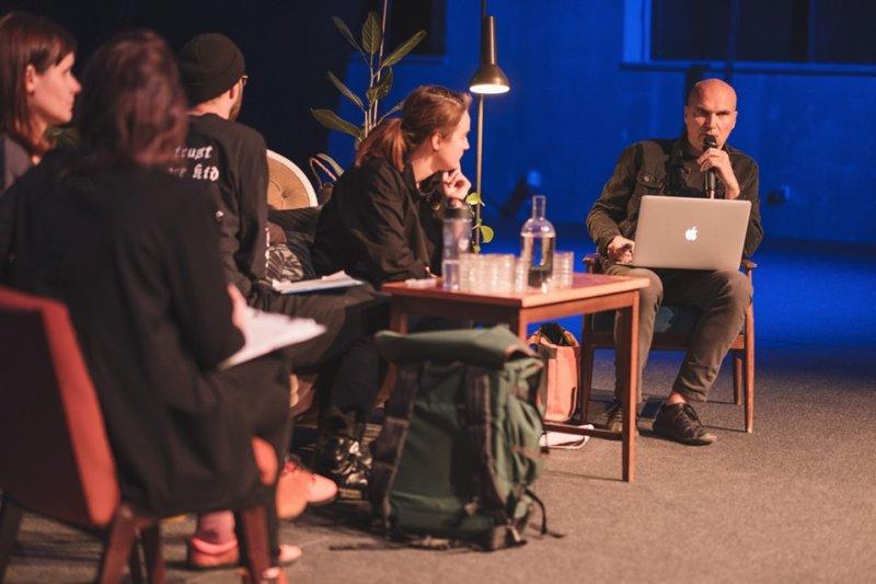 Fotografia przedstawia debatę. Jedna osoba mówi, pozostałe uważnie słuchają.