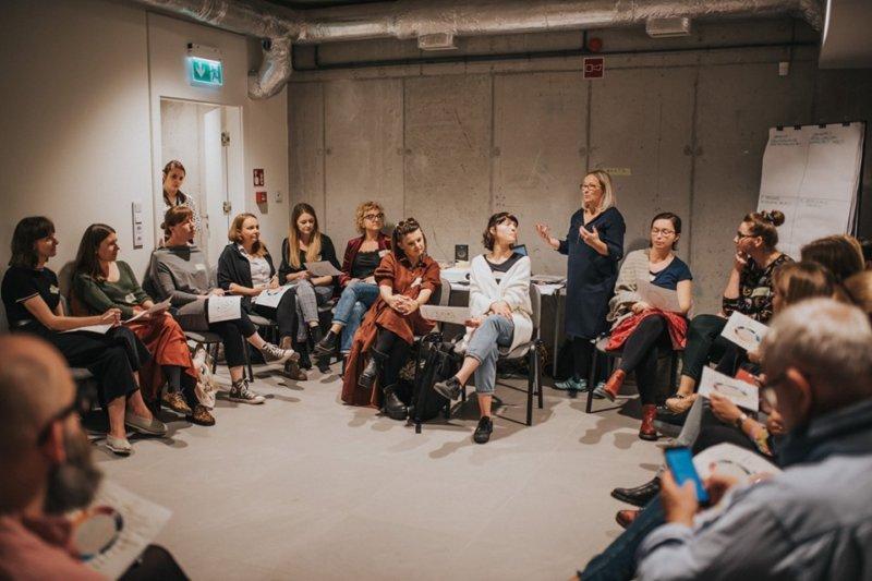 Warsztaty edukacyjne. Na zdjęciu widać dużą grupę osób siedzących w sali. Obok nich stoi prowadząca i mówi. Reszta osób słucha.