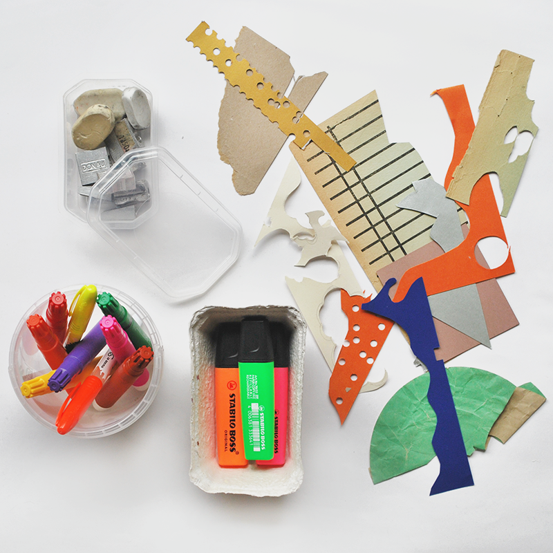 Fotografia z opakowaniami z odzysku, w których leżą mazaki, markery, temperówki.