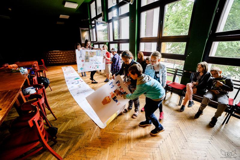 Na zdjęciu - dzieci rozkładające na podłodze gigantyczny list, który wykonały wspólnie na zajęciach.
