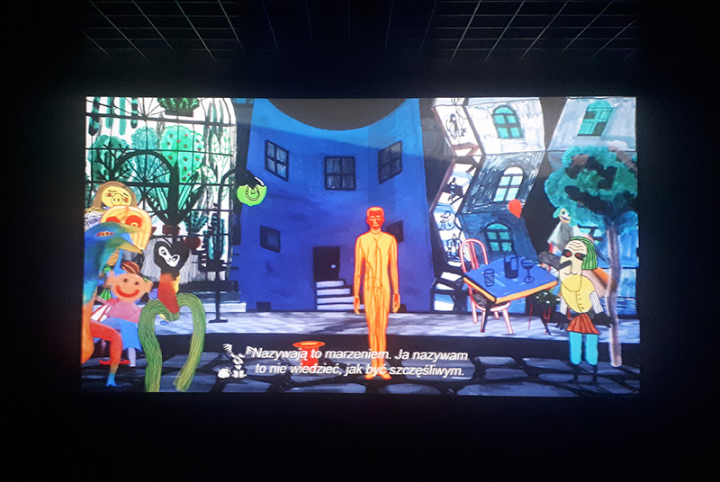 """Filmowy ekran i barwny kadr z filmu Marona. Ulica pełna postaci, w centrum - człowiek. Na dole napis """"Nazywają to marzeniem. Ja nazywam to nie wiedzieć, jak być szczęśliwym""""."""
