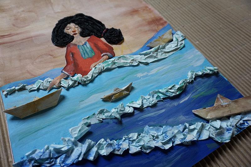 Na zdjęciu - praca przedstawiająca malowane morskie fale z pianą z udrapowanego papieru; wśród nich - papierowe łódki. W tle namalowana zadumana dziewczyna.