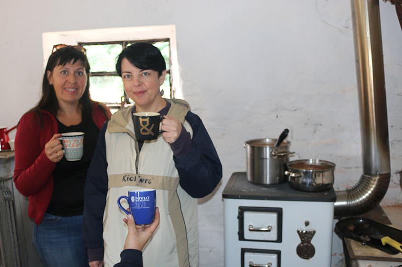 Fotografia przedstawiająca prowadzące projekt z kubkami w ręku. W tle - kuchnia ze starą, klimatyczną kuchenką.