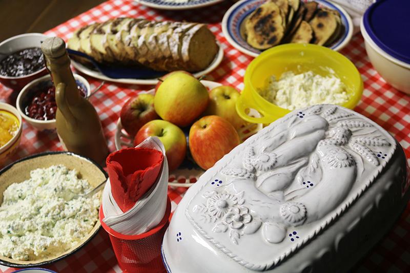 Na zdjęciu - stół nakryty kraciastym obrusem, a na nim, między innymi: jabłka, twarożek, pieczywo, powidła w miseczkach i naczynie z ozdobną ceramiczną pokrywą.