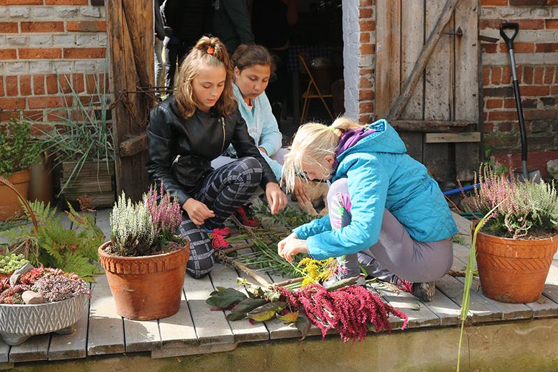 Młode uczestniczki projektu siedzą na drewnianym ganku i porządkują zerwane rośliny. Otaczają je doniczki z wrzosami.