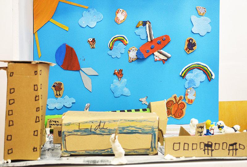 Na zdjęciu - papierowe miasto. W tle - niebo wyklejane chmurami, ptakami i latającymi maszynami wykonanymi przez dzieci.