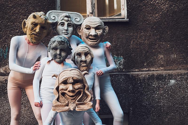 Na zdjęciu - grupa dzieci w maskach przypominających te z teatru antycznego.