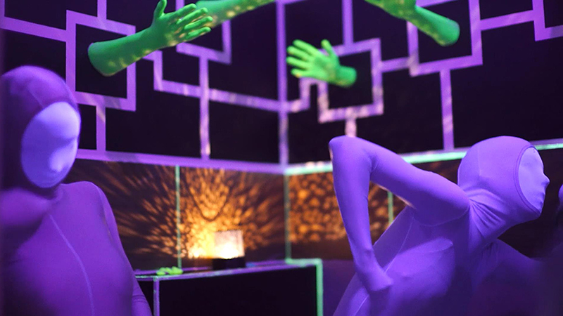 Ciemne wnętrze galerii TWORZĘ SIĘ, w którym świecą neonowe elementy: fioletowe linie na ścianach, z których wystają zielone dłonie. Na pierwszym planie - postaci w fioletowych kostiumach, zakrywających całe ciało i twarze.
