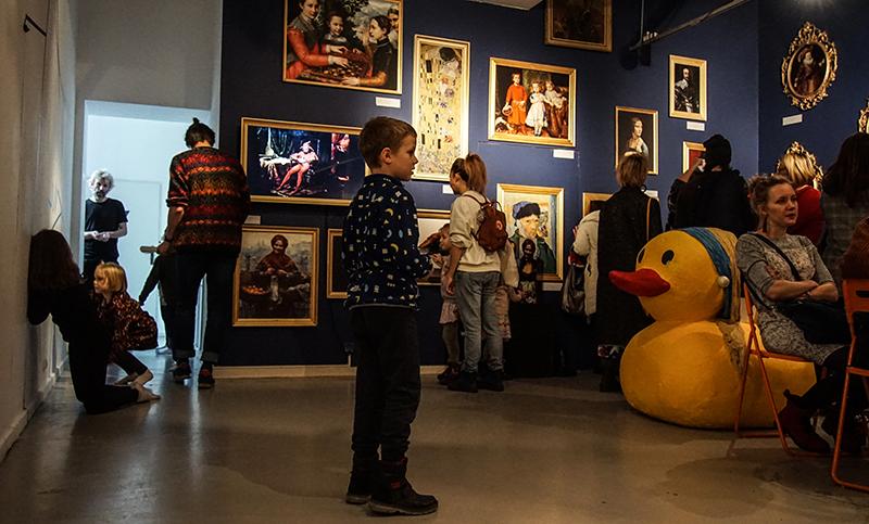Na zdjęciu: TWORZĘ SIĘ jako Muzeum po zmroku. Dzieci i dorośli w otoczeniu obrazów. W rogu sali - gigantyczna żółta kaczka.