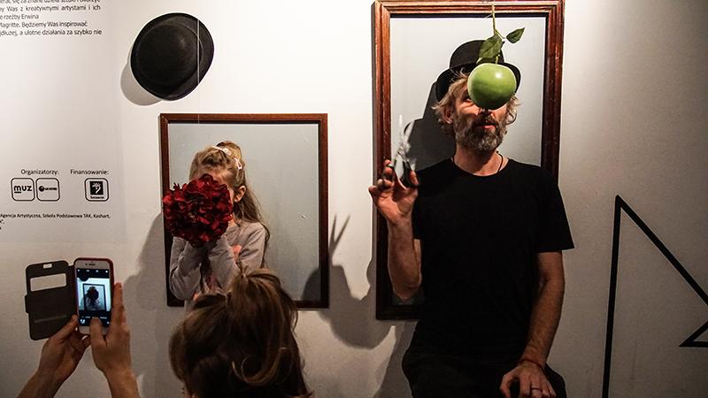 Na zdjęciu - dziewczynka zakrywająca twarz bukietem i mężczyzna, który ma twarz zasłoniętą jabłkiem. Oboje otoczeni ramami wiszącymi na ścianie - udają żywe obrazy.