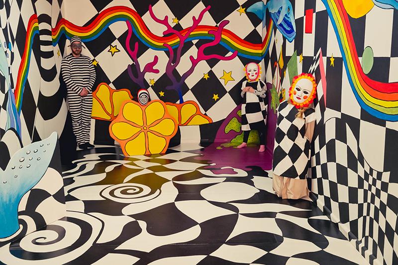Na fotografii - przestrzeń wypełniona czarno-białą szachownicą i kolorowymi wycinanymi motywami. Są tu wielkie kwiaty, jest ogon wieloryba. W lewym rogu pomieszczenia widać mężczyznę w pasiastym ubraniu. Przy jednej ze ścian stoją dzieci w fantazyjnych maskach.