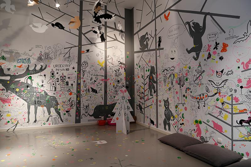 Na zdjęciu widać ściany wypełnone rysunkami dzieci i naklejkami z leśnymi zwierzętami.