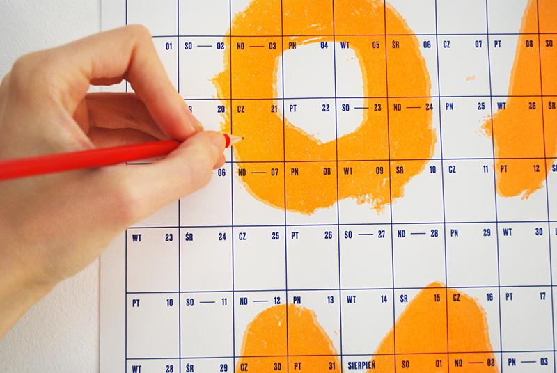 Na zdjęciu - dłoń wpisująca czerwonym ołówkiem notatkę do naściennego kalendarza.