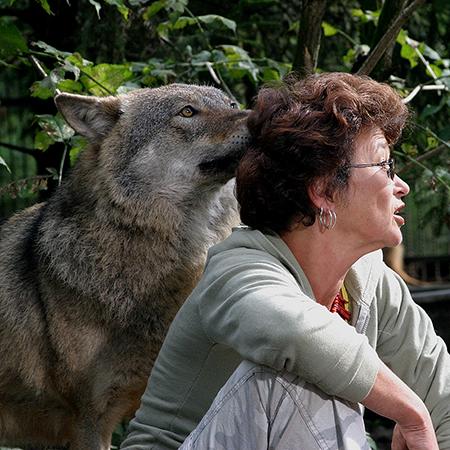 Na zdjęciu - Dorota Sumińska z wilkiem wtulającym się w jej włosy.