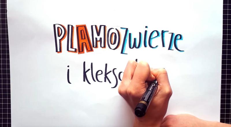 Mini warsztat Wyobraźniej - dłoń pisząca na kartce filmowy tytuł.