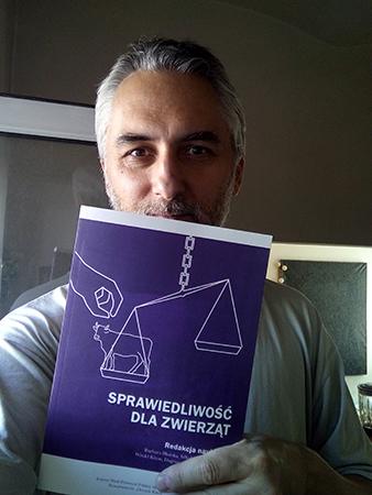 """Fotografia przedstawia Dariusza Gzyrę trzymającego książkę """"Sprawiedliwość dla zwierząt"""""""
