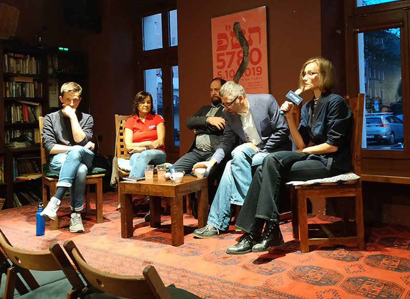 Fotografia przedstawia pięć osób siedzących przy stoliku. Jedna trzyma mikrofon.