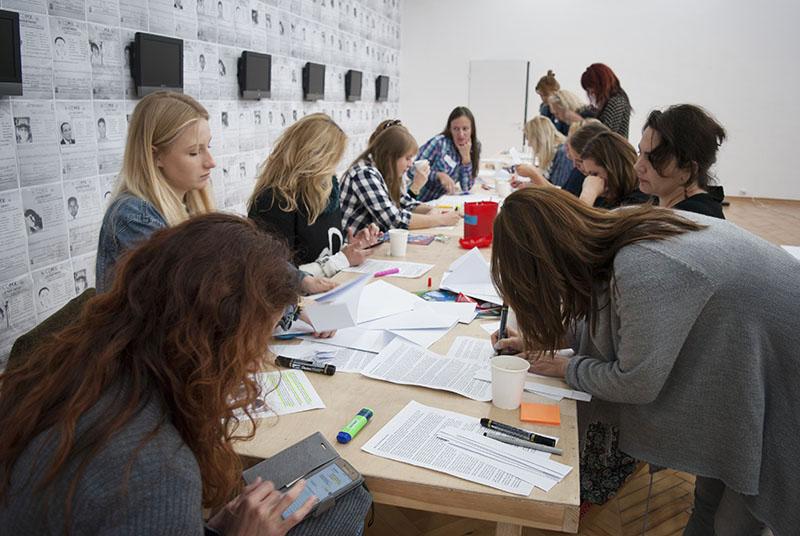 Na fotografii - grupa kobiet pracująca z notatkami przy długim stole.
